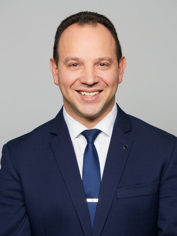 Man wearing suit and tie smiling at the camera